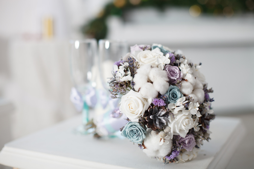 Winter wedding bouquet. Wedding bouquet of flowers lying on a chair near two wedding glasses.